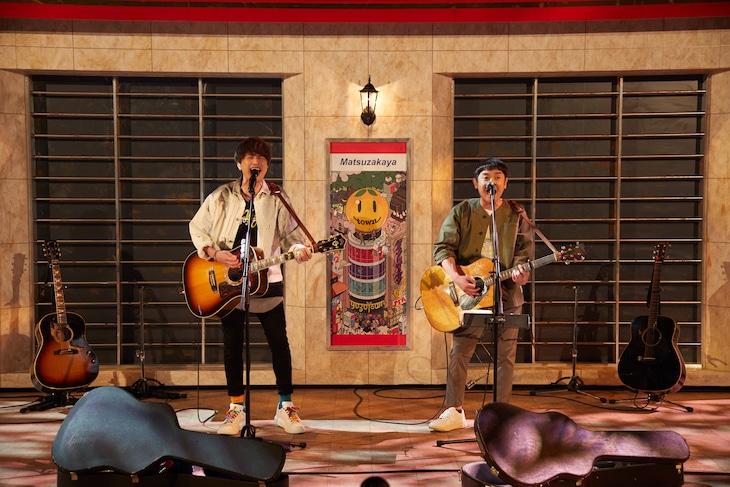 松坂屋前を再現したセットの前で歌うゆず。