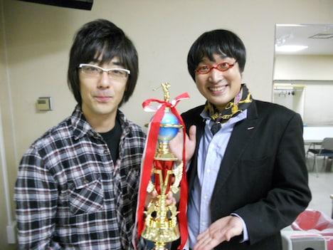 「言語遊戯王8」で優勝した東京03豊本とMCの南海キャンディーズ山里。試合中山里は「豊本さんは大きな声を出さない人というイメージ」と語り、その言葉通り豊本は終始冷静な試合運びで勝利を決めた。