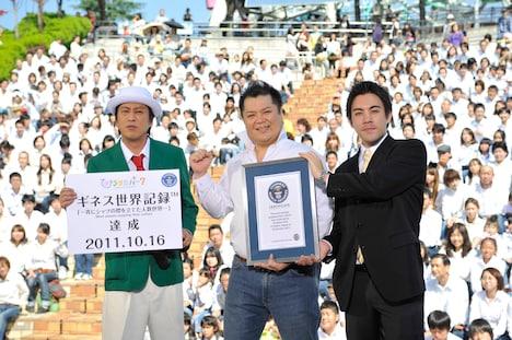 ひらかたパークを舞台にした「一斉にシャツの襟を立てた人数世界一」への挑戦で、見事ギネス記録を達成したブラックマヨネーズと、2人に認定証を渡すギネス公式認定員のショーン・カニーン氏(左から)。