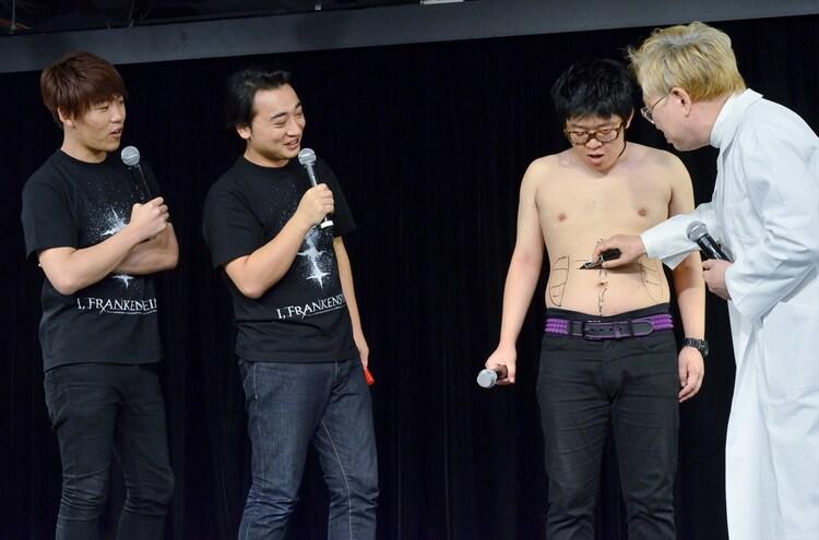 高須院長(右端)に肉体改造のプランを油性ペンで書き込まれるトンファー山西(右から2人目)。
