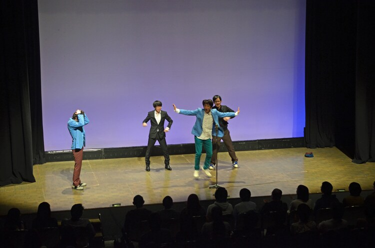 「ホリケンサイズ」を踊る堀内(中央)と頭を抱える瀧上(左)。