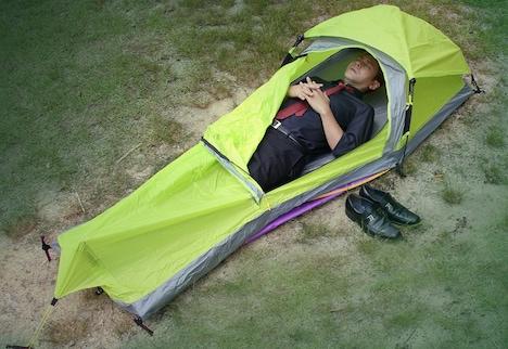 1人用テント「ワンタッチソロテント」に横たわるヒロシ。