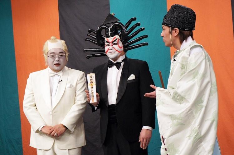 サンドウィッチマンに櫻田山神社のお札を手渡す狩野英孝(右)。