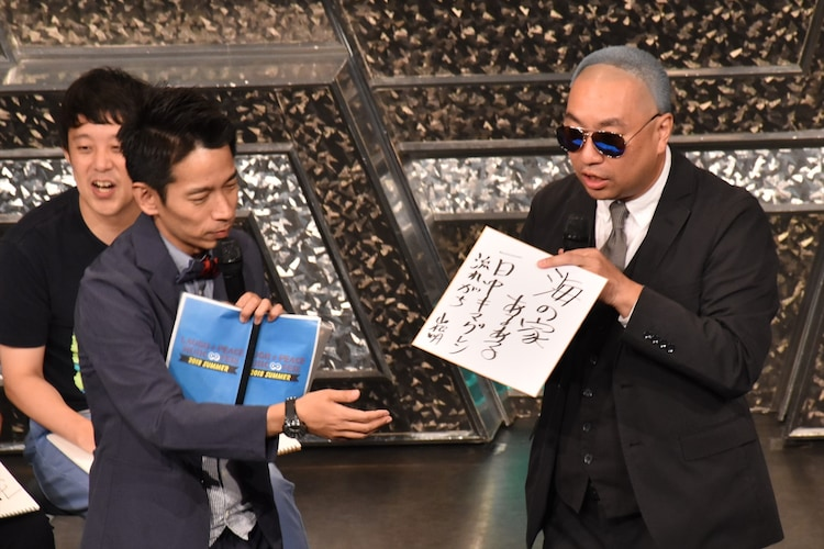 「海の家あるある」を書いた色紙を、お題を提供したファンにプレゼントするレイザーラモンRG(右)。