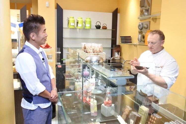 フランス・パリ市内のパンとスイーツの店の店主にかつおぶしを渡す勝俣州和(左)。(c)SBS
