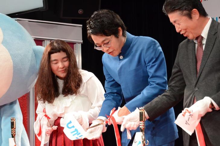 テープカットに手こずるゆにばーす川瀬名人(中央)と心配そうに見ている相方のはら(左)。