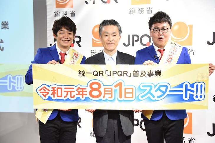 JPQR広報大使に就任した銀シャリと総括審議官・秋本芳徳氏(中央)。