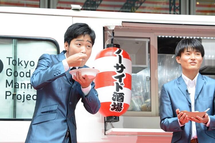 「ノーサイ丼」を試食するジャルジャル後藤(左)。
