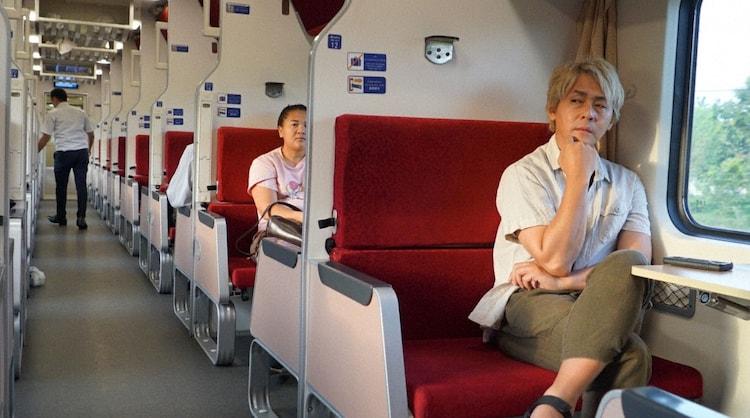 「迷宮グルメ 異郷の駅前食堂」で列車に乗るヒロシ。(c)BS朝日
