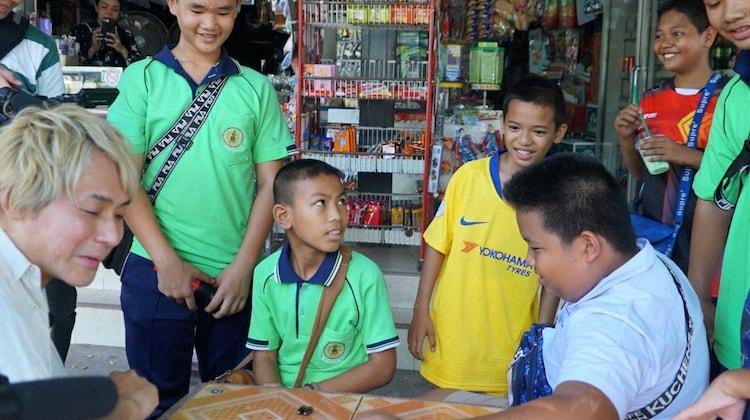 「迷宮グルメ 異郷の駅前食堂」でタイを訪れ、子供たちにおもちゃを買うヒロシ(左端)。(c)BS朝日