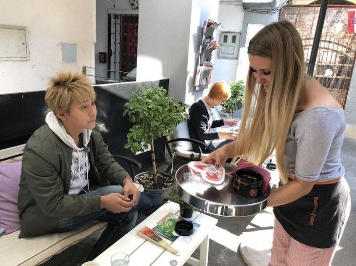 「迷宮グルメ 異郷の駅前食堂」でクロアチアを訪れ、愛する人への贈り物として用いられるハート型のクッキーを、カフェで出会った女性にプレゼントするヒロシ。(c)BS朝日