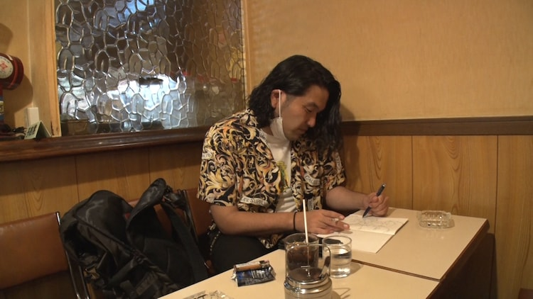 喫茶店でエッセイ執筆に取り組む見取り図・盛山。