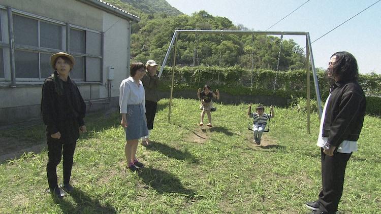 2019年山口県上関町の旅より、休校中の校庭で遊ぶ家族に話しかけるピース又吉。