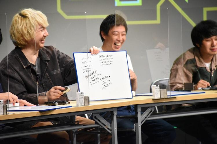 板書を写したホワイトボードを見せる三四郎・相田(左)。