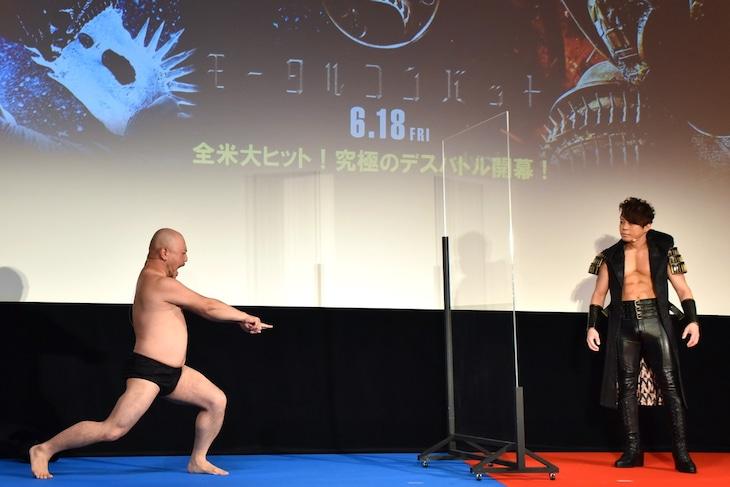 映画「ハリウッドザコシショウ」の公開直前イベントで、作品の魅力を伝えるべく「誇張しすぎたフェイタリティ」を披露するハリウッドザコシショウ(左)。右は西川貴教。