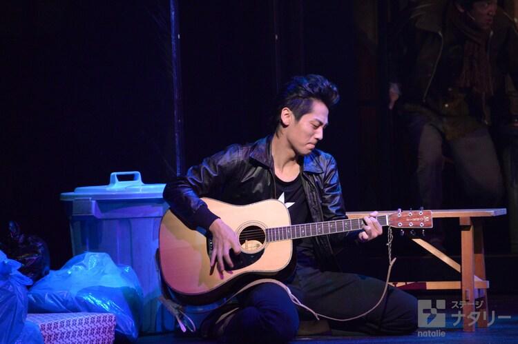 「俺節」フォトコールより、ギターを弾く南風原太郎(福士誠治)。