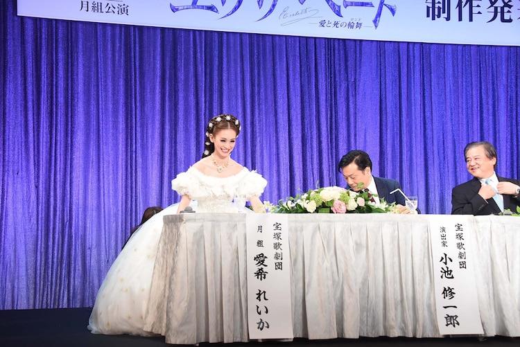 宝塚歌劇月組「ミュージカル『エリザベート―愛と死の輪舞(ロンド)―』」制作発表会より、ドレスのボリュームでなかなか着席できない愛希れいか(左)と、心配してのぞき込む小池修一郎(右から2番目)。
