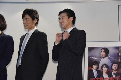 金児憲史のものだというネクタイを示す岩永ジョーイ(中央)。