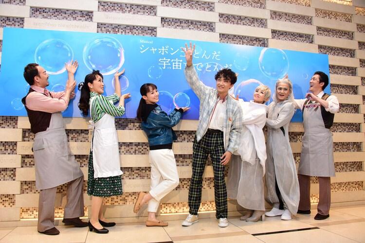 カメラマンのリクエストに応じ、看板に描かれたシャボン玉に触れるようにポーズをとる出演者たち。