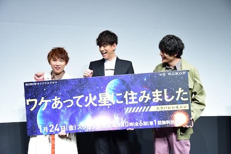 ガッツポーズを求められ、パネルを片手で持つことになり戸惑う須賀健太(左)、三浦翔平(中央)、崎山つばさ(右)。
