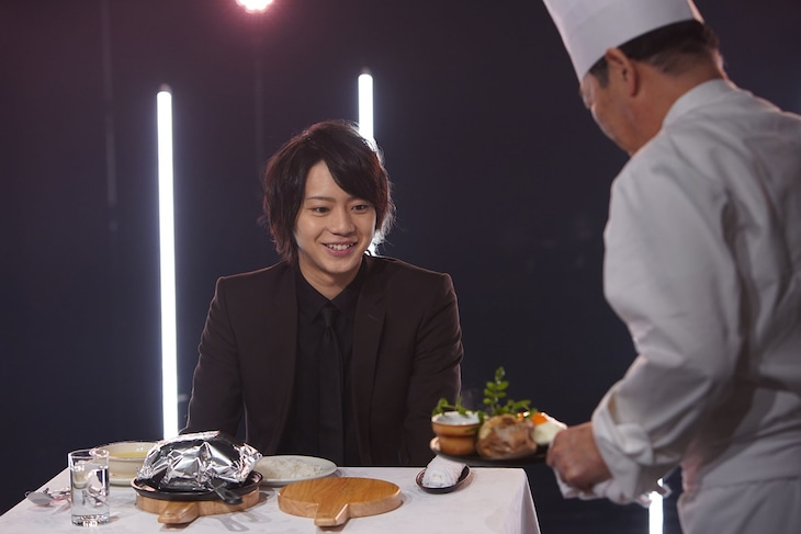 NHK総合「ごちそう男子」より、運ばれてきたハンバーグを目にしてほほ笑む佐藤流司。(写真提供:NHK)