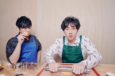 生地を伸ばしていく鈴木崚汰と、試作品のクッキーをつまみ食いする古川慎。
