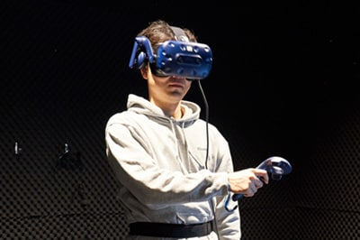 クラスター社で使用されているVRデバイスを着用した加藤CEO。HMDのほか、手や足の動きをトラッキングするトラッカーも身につけている。