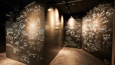 クラスターの社内風景。壁には多数のバーチャルタレントによるサインが。