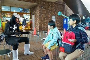 撮影現場にて、子供たちと話す三元雅芸。