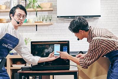 アプリ「キッチンポケット」を操作する佐野岳(右)。