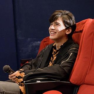 1分間挨拶をする坂東龍汰を、客席に座って見守る才川コージ。
