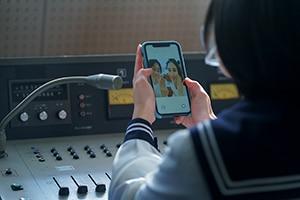 倉木(田村健太郎)と彼の妻(橋本マナミ)が映るスマートフォン画面。
