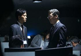 「新聞記者」に登場する内閣情報調査室。松坂桃李演じる杉原(左)、田中哲司演じる多田(右)。
