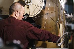 映写室の窓から手を伸ばして撮影する塚本晋也。