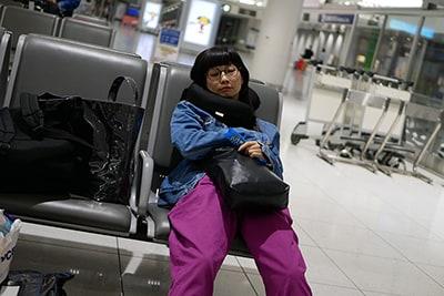 疲れて空港で眠るユイ・ガ・ドクソン。
