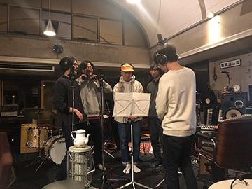 コーラスのレコーディングをするバンドメンバー。