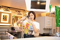 カウンターでジンジャーエールをカップに注ぐ杏沙子。
