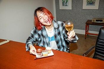 ワイングラスを片手に微笑む下川リヲ(Vo, G)。
