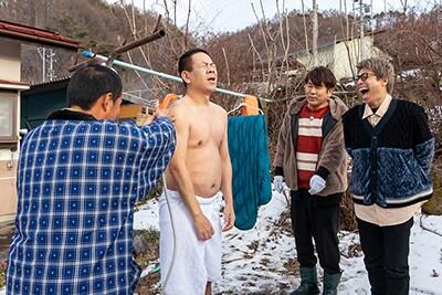 FUJIWARA原西(左から2人目)が屋外でシャワーを浴びる様子。